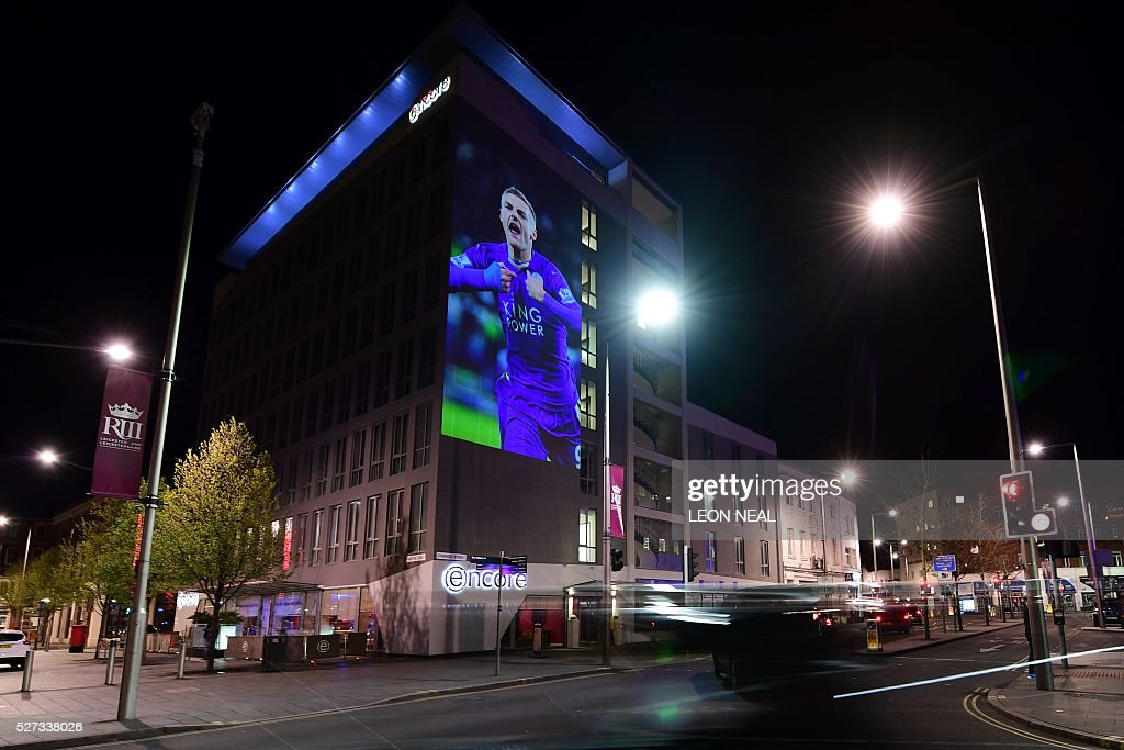 A large projection of an image of Leicester City's striker Jamie Vardy is seen on the side of a building as the city celebrate's their team becoming the English Premier League champions in central Leicester, eastern England, on May 2, 2016. Leicester City completed their fairytale quest for the Premier League title on May 2 after Eden Hazard's stunning late goal earned Chelsea a 2-2 draw with second-place Tottenham Hotspur. NEAL