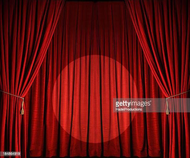 Cortinas rojas grandes de teatro con foco