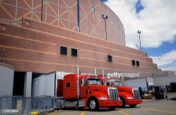 2 large red trucks parked outside a brick building