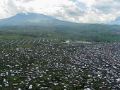Large Refugee camp on a recent volcanic lava field near Goma Republic of Congo and active Volcano in the background within the Virunga National Park and part of the Virunga Mountains