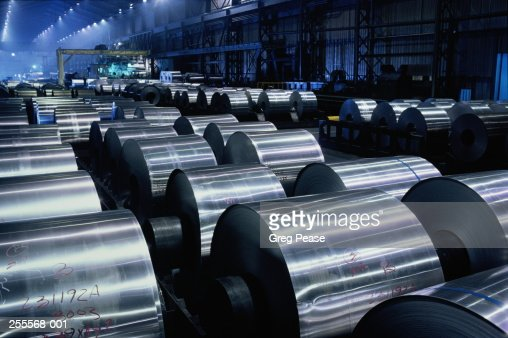Large rolls of sheet aluminium stored on factory floor