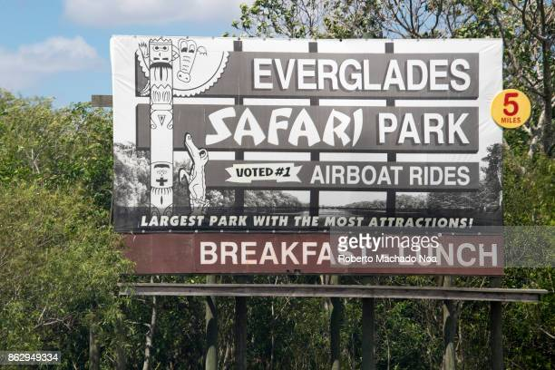 Large signboard of Everglades safari park it's fixed on iron and wooden frame amid trees and gives all the details about the park