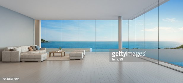 Large sofa on wooden floor near glass window and swimming pool with terrace at penthouse apartment, Lounge in sea view living room of modern luxury beach house or hotel : Stock Photo