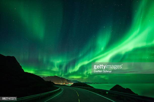 Large spectacular Northern Lights over road & sea