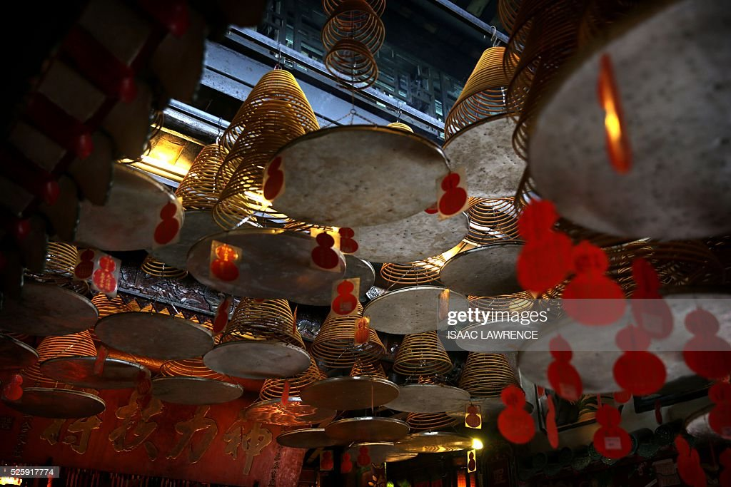 Large spiral joss sticks hang from the ceiling inside the Joss House Bay Tin Hau temple during celebrations for the Tin Hau Festival in Hong Kong on April 29, 2016. Tin Hau is the Goddess of the Sea and patron saint of fishermen - On her birthday, locals flock to the more than 70 temples dedicated to her to pray for safety, security, fine weather and full fishing nets during the coming year. / AFP / ISAAC