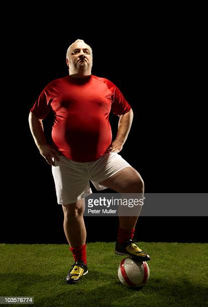 Large sportsman with foot on football