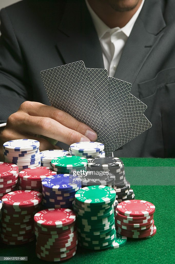 Large stack of poker chips in front of man playing cards, close-up : Stock Photo