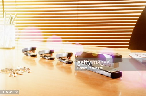 Large stapler followed by three smaller staplers. : Stock Photo