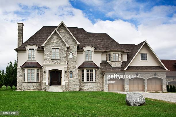 Large stone home with green lawn under blue sky