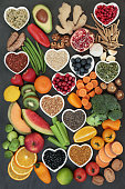 Large super food collection high in antioxidants, vitamins, anthocyanyns, fiber and minerals with fresh fruit, vegetables, seeds, nuts, grains, cereals, pulses, bee pollen grain, herbs and spices.