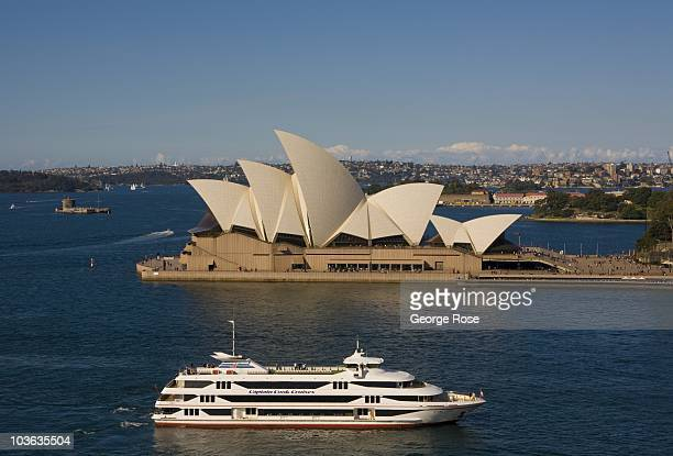 A large Sydney Harbour tour boat travels past the iconic Sydney Opera House on August 8 2010 Sydney AustraliaThe multiuse performing arts venue...