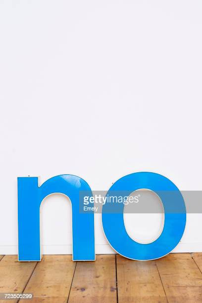 Large three-dimensional letters on wooden floor spelling the word NO