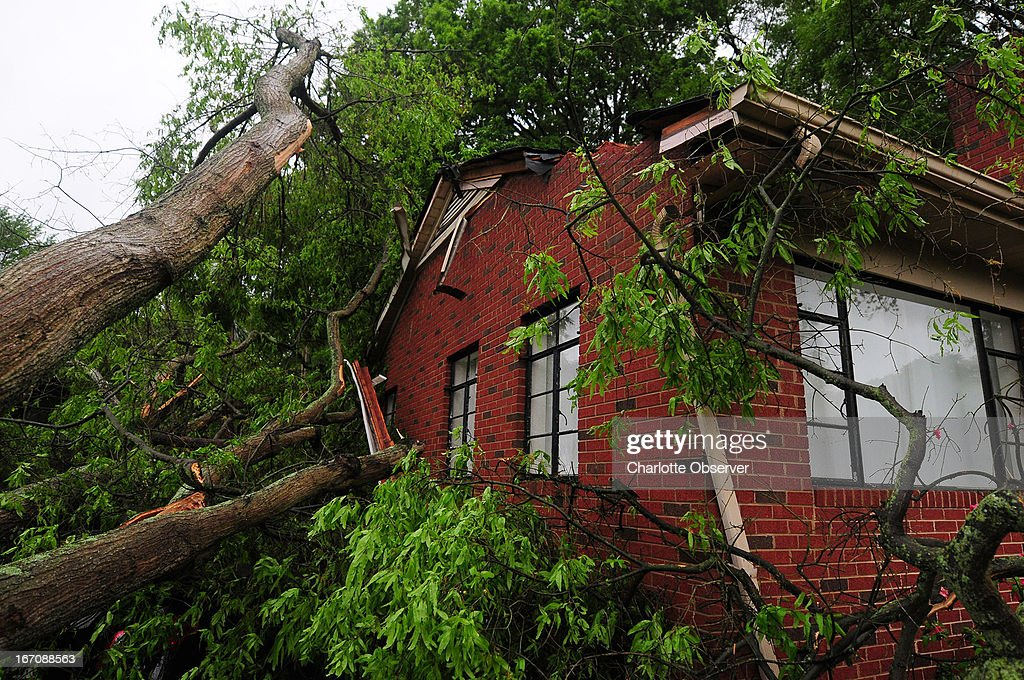 A large tree covers a section of a home on Shamrock drive in Charlotte, North Carolina, following a strong storm on Friday, April 19, 2013.