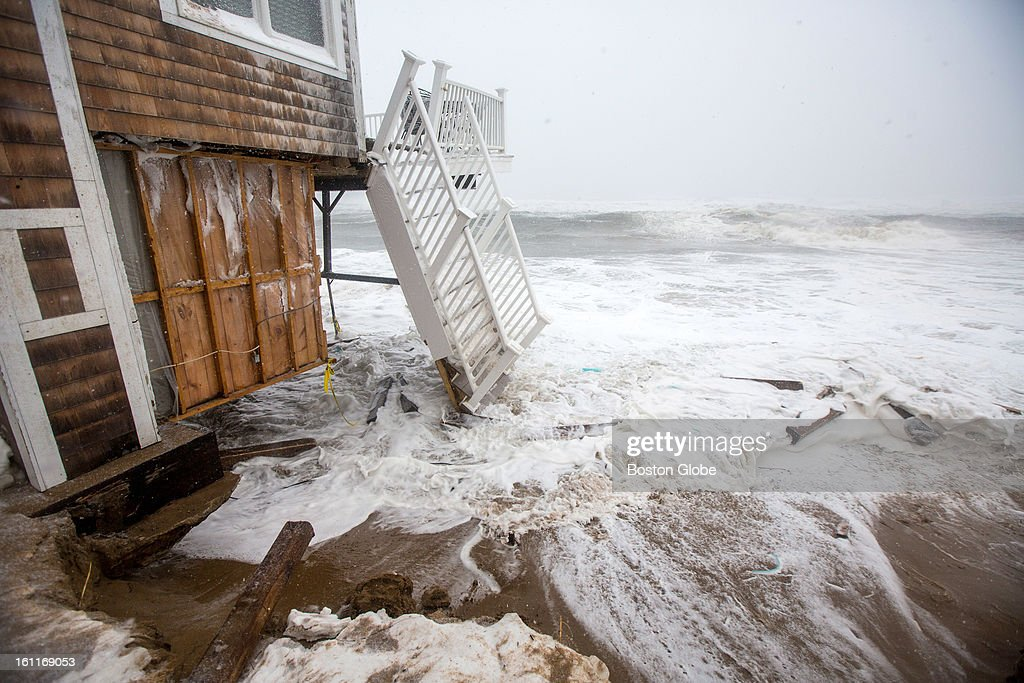 Large waves crashed over sand barriers, destroying the decks of homes along the beach on Plum Island, as a large winter storm hit the region.