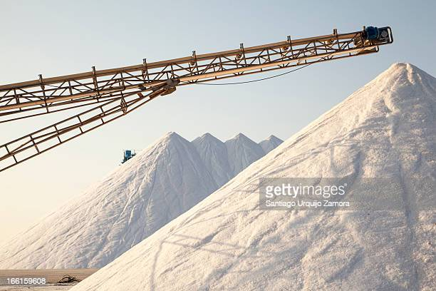 CONTENT] Large white conical shaped piles of salt and some machinery for its extraction on a salt factory in Santa Pola Valencian Community Spain