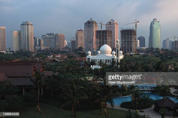 A large white mosque stands out at dusk against the Jakarta skyline In front can be seen the gardens and the swimming pools of the ShangriLa Hotel