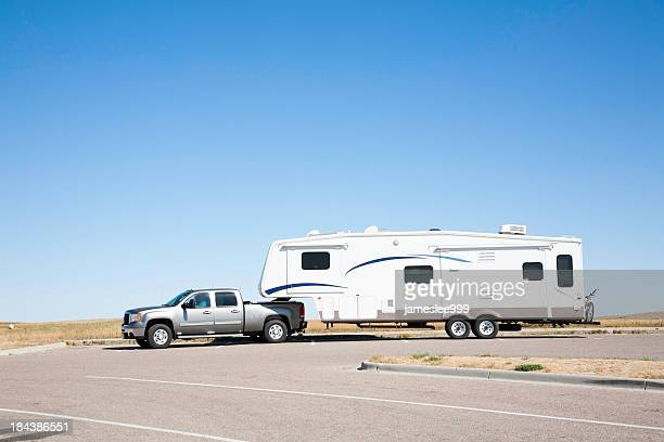 Large white RV trailer hitched to a double cab gray truck