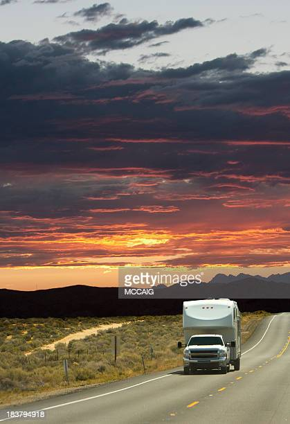 A large white truck driving down a road at sunset