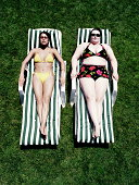 Large woman lying beside slim woman on sun loungers, elevated view
