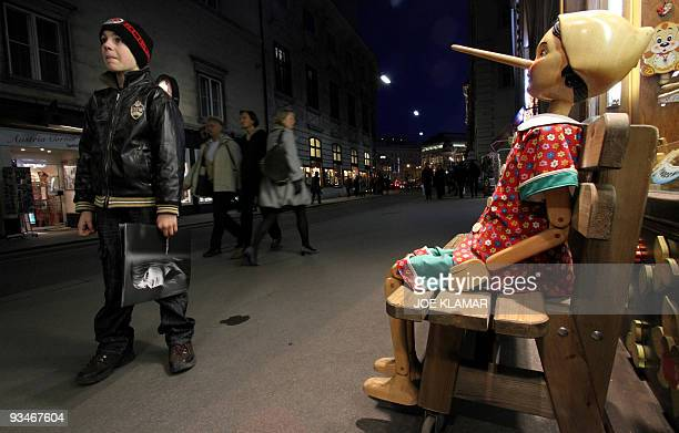 A large wooden Pinocchio puppet attracts customers into a shop selling wooden art in the city centre of Vienna on November 28 2009 AFP PHOTO / JOE...