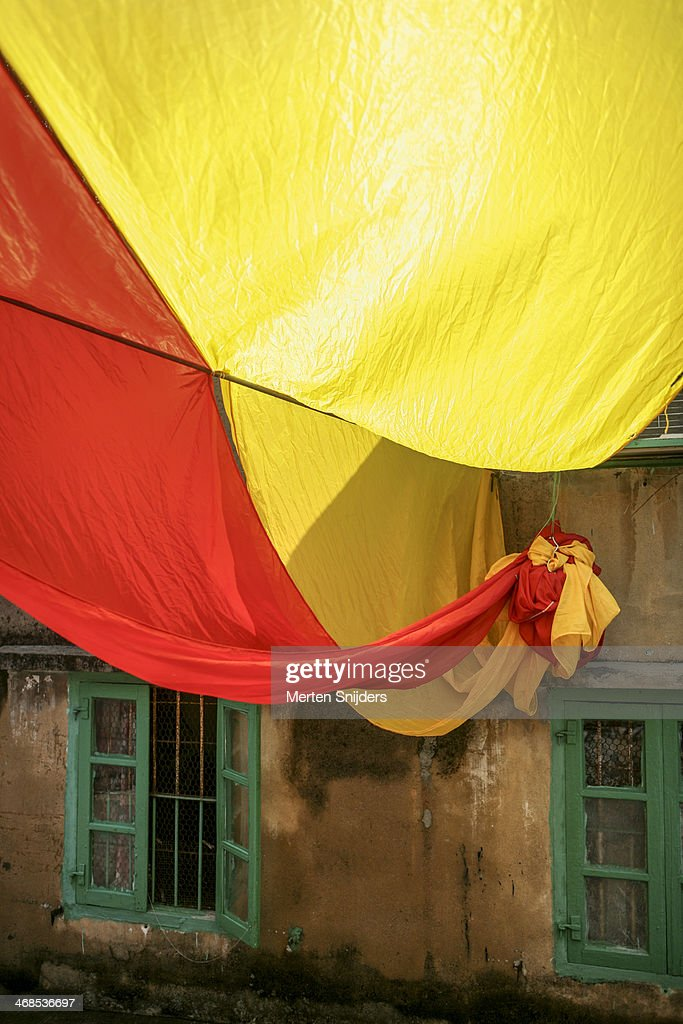 Large yellow and red flag in alley : Stock Photo