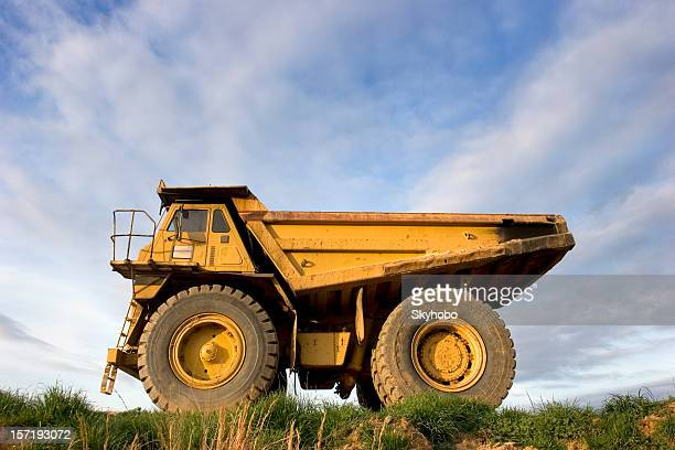 A large yellow dump truck against a cloudy sky