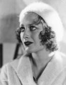 Largeeyed film star Joan Crawford wearing a fluffy white beret and coat to match