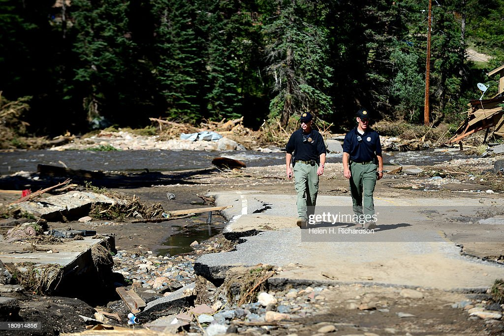 Larimer County Deputy Sheriff's Jack Newton, left and Brad Harkin, right, walk along the damaged end of Main Street in Glen Haven, Co, on September 17, 2013. The road, which is Colorado Road 43, is a river the rest of the way to Drake and Highway 34. The small mountain town of Glen Haven north east of Estes Park has been wiped out by the recent and massive flooding.