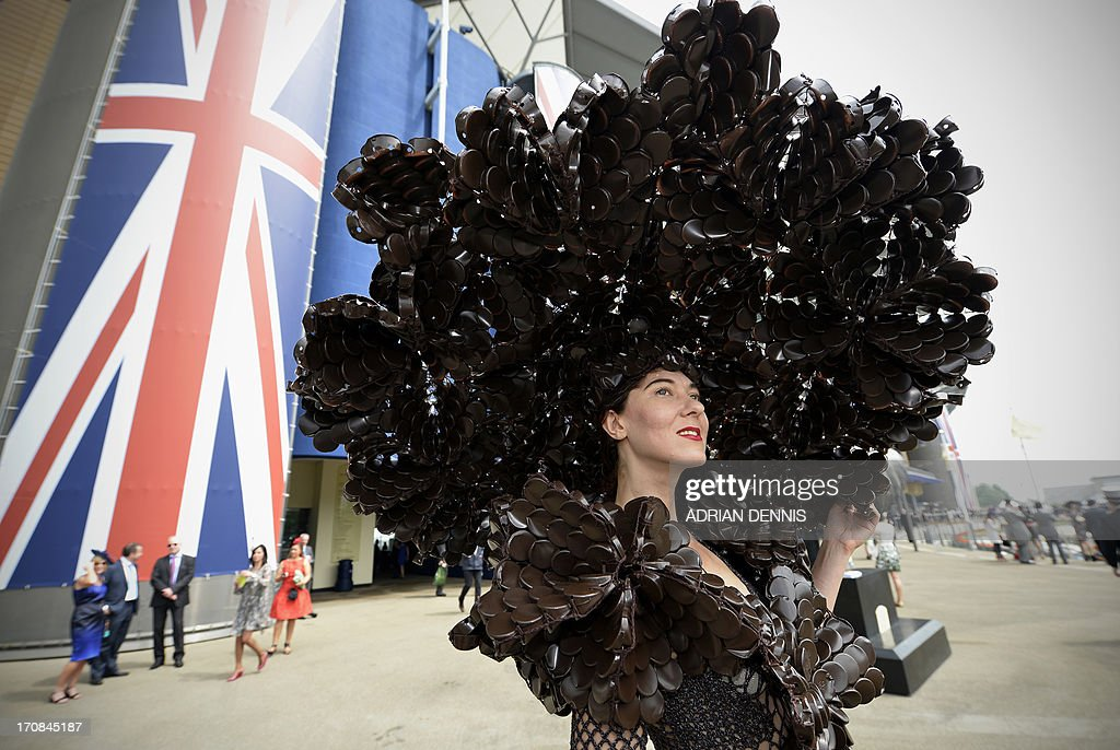 Larisa Katz, wearing an outfit made from chocolate packaging, poses for a photograph during the second day of Royal Ascot, in Berkshire, west of London, on June 19, 2013. The five-day meeting is one of the highlights of the horse racing calendar. Horse racing has been held at the famous Berkshire course since 1711 and tradition is a hallmark of the meeting. Top hats and tails remain compulsory in parts of the course while a daily procession of horse-drawn carriages brings the Queen to the course. AFP PHOTO / ADRIAN DENNIS