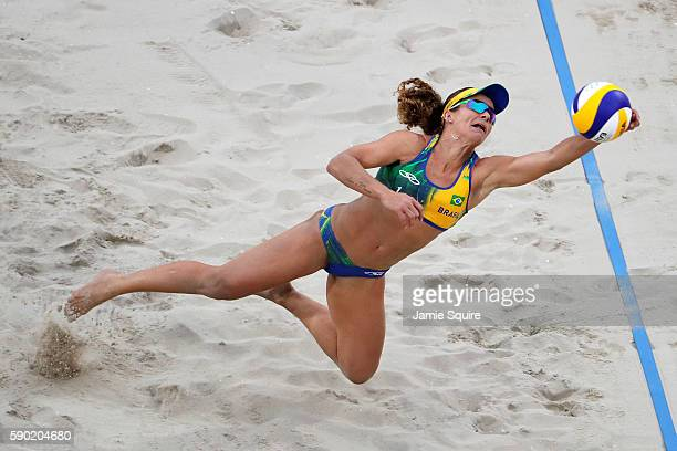 Larissa Franca Maestrini of Brazil picks up the ball on the playing against Laura Ludwig and Kira Walkenhorst of Germany during the beach volleyball...