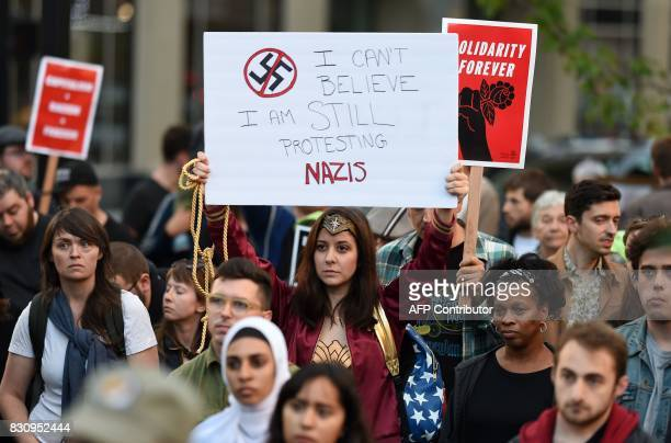 Larissa Roberts holds up a sign as hundreds of protesters gather to march against racism in Oakland California on August 12 2017 Protesters marched...