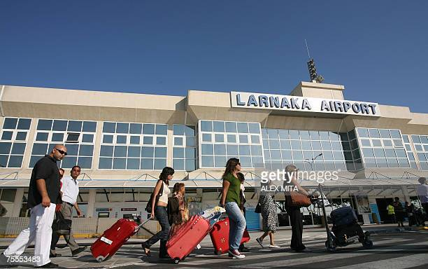 Tourists arrive at Larnaca International Airport 19 July 2007 A row over increased service fees at Cyprus' airports which threatened to leave...