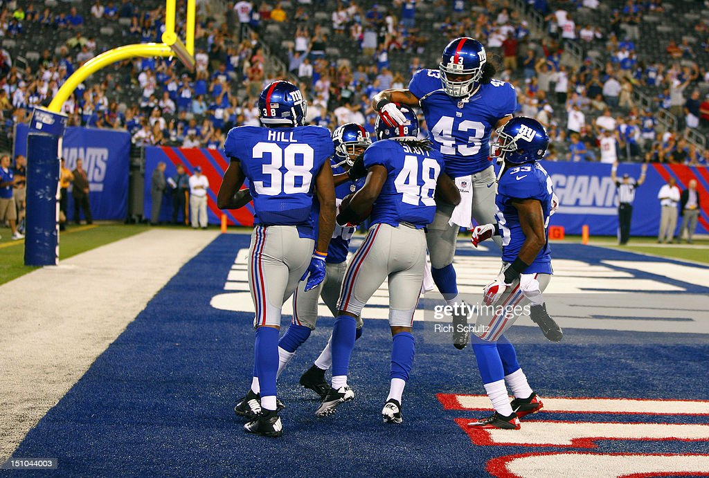 Laron Scott of the New York Giants is congratulated by teammate Brandon Bolden Justin Tryon Jake Muasau and Dante Hughes after Scott intercepted a...