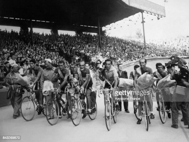 A l'arrivée du Tour de France au Parc des Princes l'équipe italienne fait le tour d'honneur Fausto Coppi le vainqueur au centre porte un bouquet de...