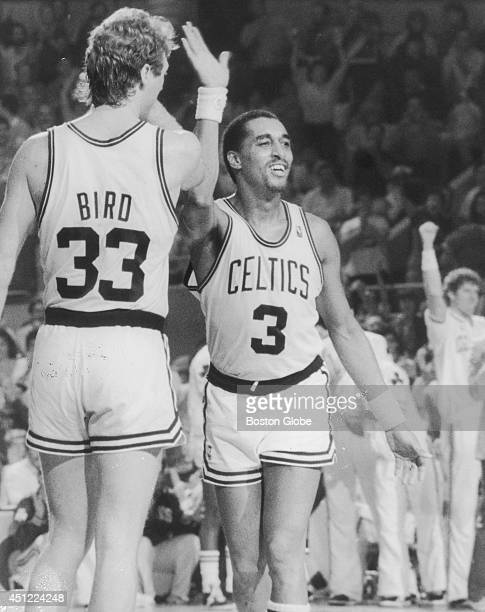Larry Bird congratulates Dennis Johnson on winning a game