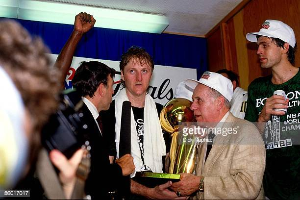 Larry Bird of the Boston Celtics and Red Auerbach President and General Manager of the Boston Celtics hold the 1986 NBA Championship trophy while...