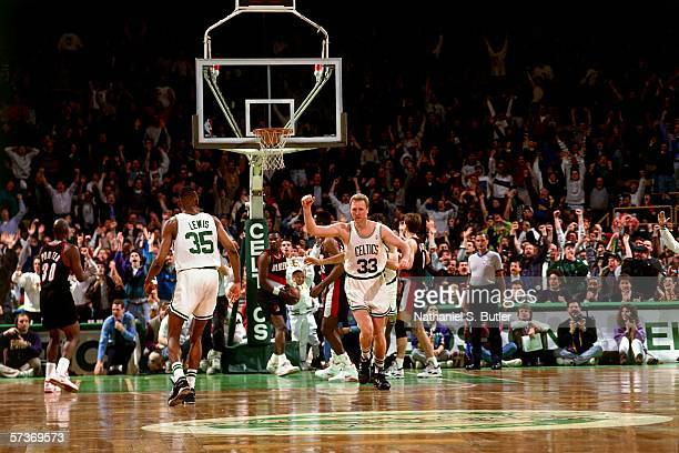 Larry Bird of the Boston Celtics celebrates with teammate Reggie Lewis during a game against the Portland Trailblazers in 1991 at the Boston Garden...