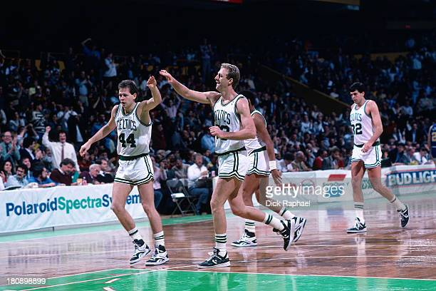 Larry Bird of the Boston Celtics congratulates teammate Danny Ainge as the exit the court during a game circa 1986 at the Boston Garden in Boston...