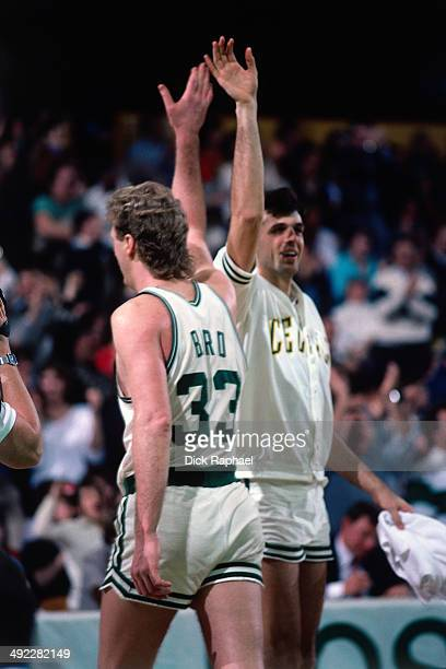 Larry Bird of the Boston Celtics gives his teammate Kevin Mchale a high five during a game circa 1986 at the Boston Garden in Boston Massachusetts...