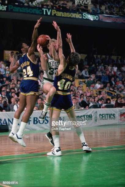 Larry Bird of the Boston Celtics goes up for a shot against defenders George Johnson and Steve Stipanovich of the Indiana Pacers during a game played...