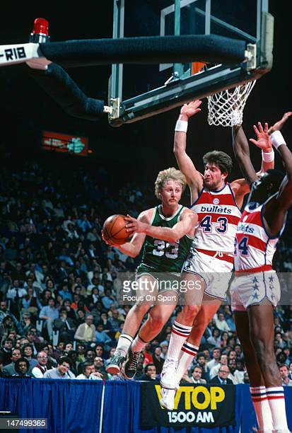 Larry Bird of the Boston Celtics goes up on Jeff Ruland and Spencer Haywood of the Washington Bullets during an NBA basketball game circa 1983 at the...