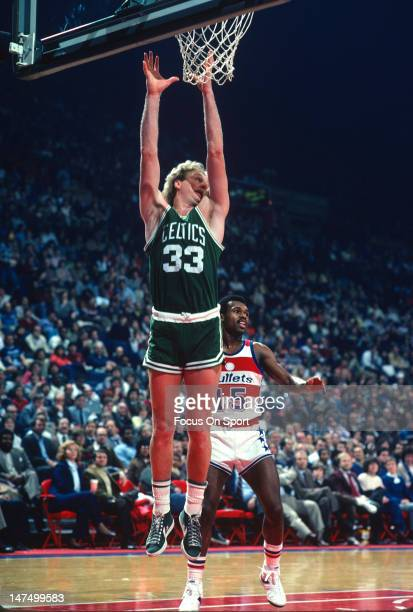 Larry Bird of the Boston Celtics goes up to grab a rebound in front of Frank Johnson of the Washington Bullets during an NBA basketball game circa...