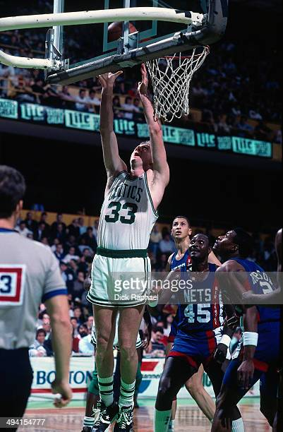 Larry Bird of the Boston Celtics grabs a rebound against the New Jersey Nets during a game played circa 1990 at the Boston Garden in Boston...