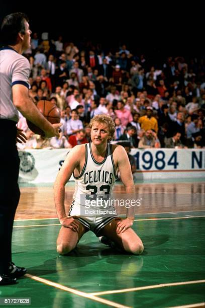 Larry Bird of the Boston Celtics kneels on the ground while he looks at the referee during a game circa 1984 at the Boston Garden in Boston...