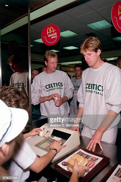 Larry Bird of the Boston Celtics left waits to pay for some food at a McDonald's on their day off during the 1988 McDonald's Open circa 1988 in...