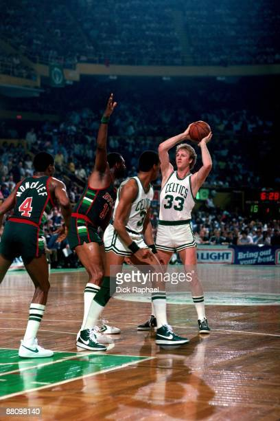 Larry Bird of the Boston Celtics looks to pass against Bob Lanier of the Milwaukeee Bucks during a game played in 1984 at the Boston Garden in Boston...