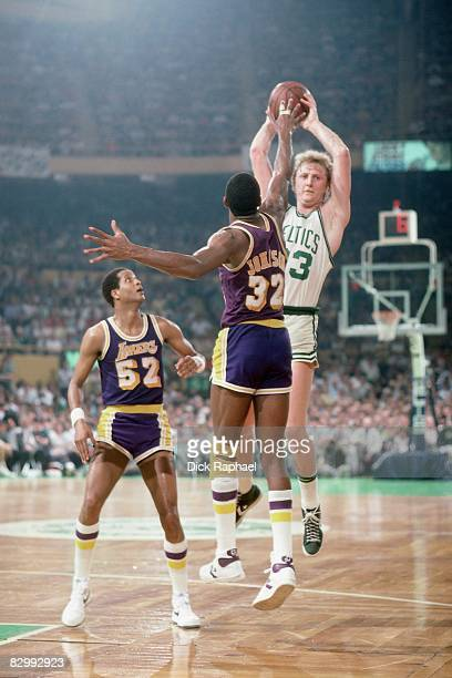 Larry Bird of the Boston Celtics passes against Magic Johnson of the Los Angeles Lakers in Game Five of the 1984 NBA Finals played on June 8 1984 at...