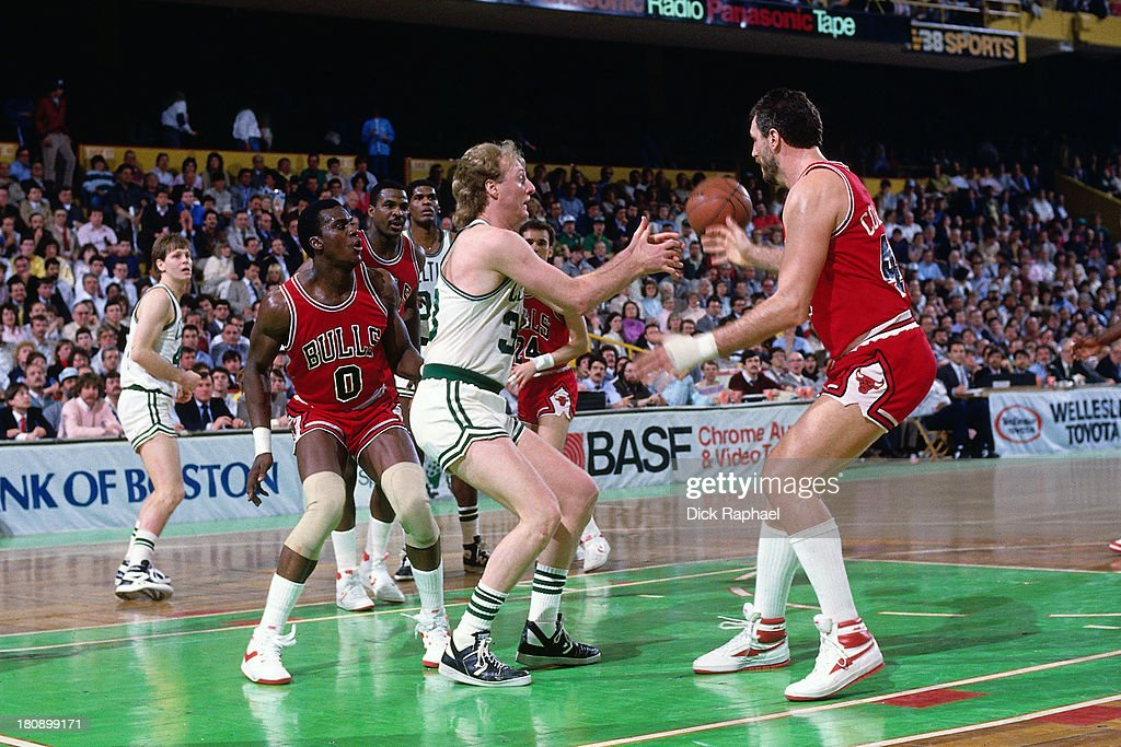 Larry Bird of the Boston Celtics receives a pass while Orlando Woolridge and Dave Corzine of the Chicago Bulls look on during a game circa 1986 at...