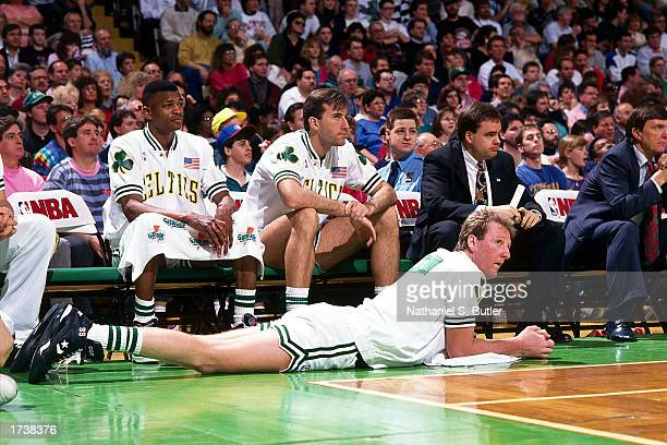Larry Bird of the Boston Celtics rest his back in front of the Celtic's bench during an NBA game at the Boston Garden on January 1 1990 in Boston...