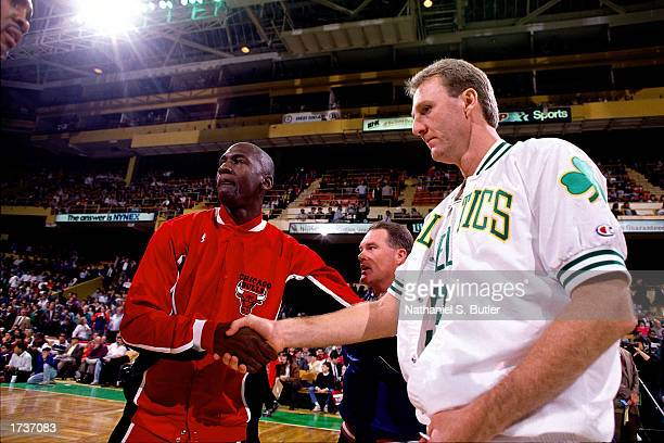 Larry Bird of the Boston Celtics shakes hands with Michael Jordan of the Chicago Bulls during the NBA pregame warmups at The Boston Garden on January...